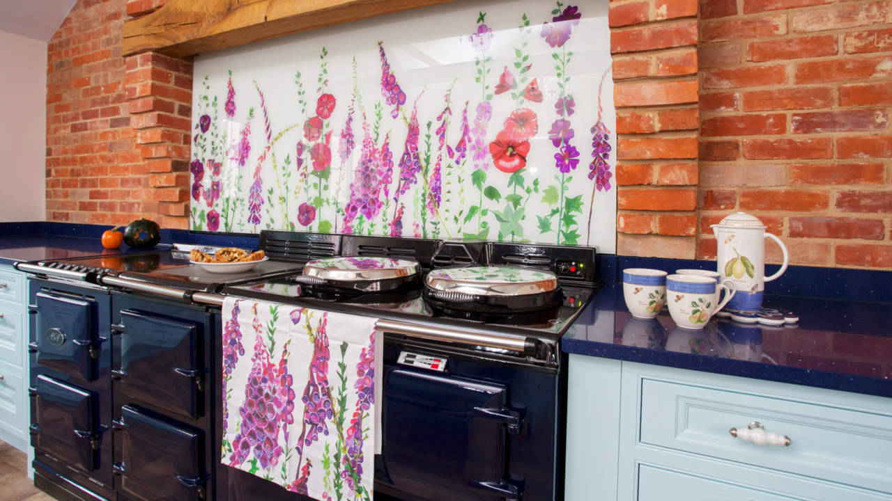 Bright floral glass bespoke splashbacks with poppies and foxgloves behind an Aga in a blue country kitchen