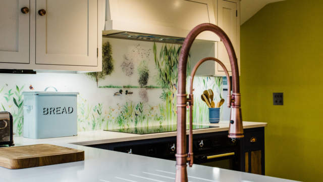 Bespoke glass splashback in country kitchen, with sink and hob